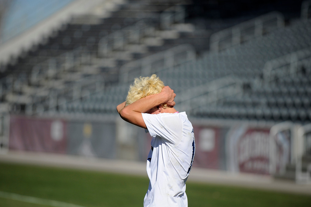 . DENVER CO: Nov. 9, 2013  Air Academy player Conner Claus hold his head and walks across the field after losing the 4A State Championship game to Cheyenne Mountain.  (Photo By Erin Hull/The Denver Post)