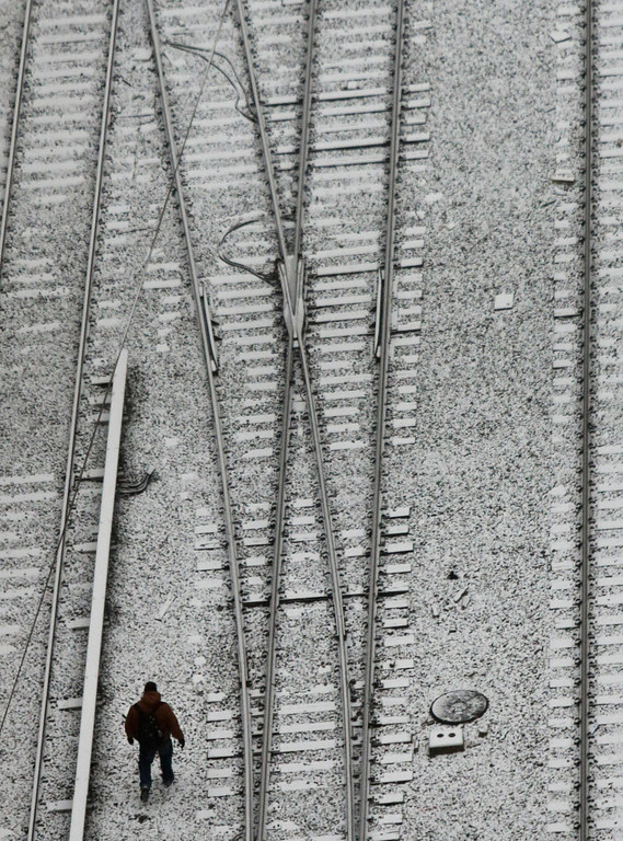 . A man walks between rail tracks near Penn Station as snowfall blankets the area on Tuesday, Jan. 21, 2014 in New York.  The National Weather Service is predicting about 8 to 12 inches of snow accumulation through Wednesday. (AP Photo/Bebeto Matthews)