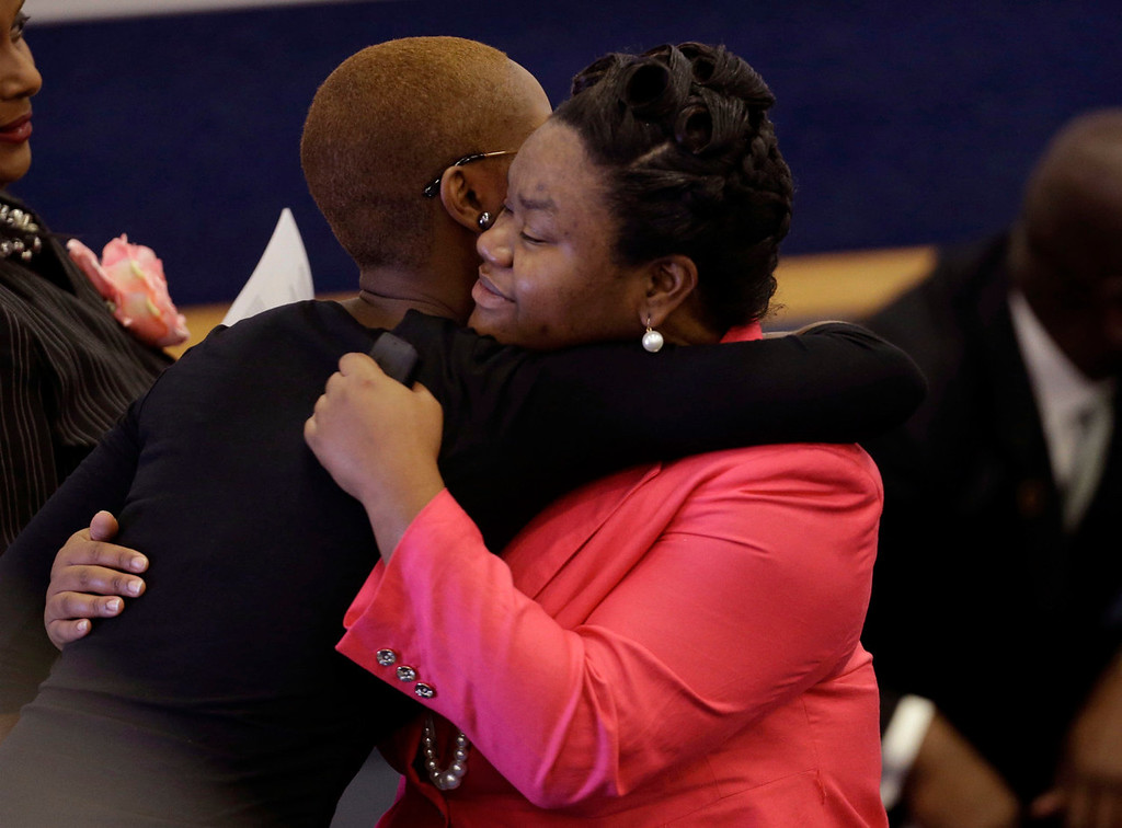 . Brandalyn Johnson, right, guardian of 6-year-old murder victim Ahlittia North, is hugged by visitors at funeral services for Ahlittia in Gonzales, La., Monday, July 22, 2013. Ahlittia was stabbed to death after disappearing from her mother\'s suburban New Orleans apartment more than a week ago. Her body was found days later. (AP Photo/Gerald Herbert)