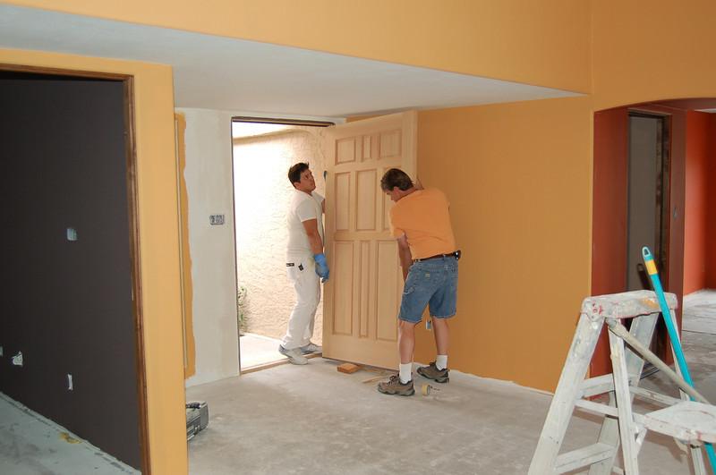 It takes every bit of Vladi's and Tom's effort to hang that front door.