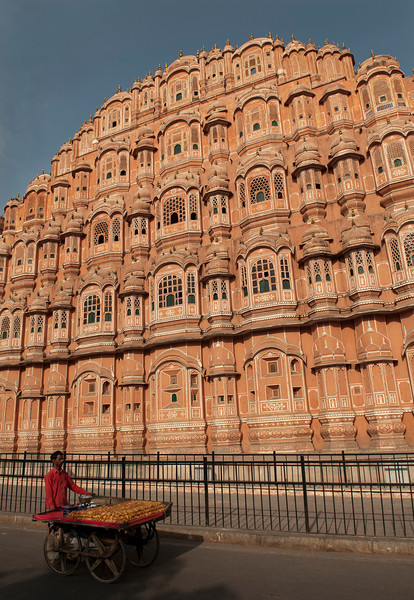 "Hawa Mahal ""Palace of Winds""  is a palace in Jaipur.  It was built in 1799 by Maharaja Sawai Pratap Singh, and designed by Lal Chand Usta in the form of the crown of Krishna, the Hindu god. Its unique five-storey exterior is also akin to the honeycomb of the beehive with its 953 small windows called jharokhas that are decorated with intricate latticework. The original intention of the lattice was to allow royal ladies to observe everyday life in the street below without being seen, since they had to observe strict ""purdah"" (face cover).