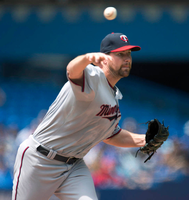 . Minnesota Twins pitcher Mike Pelfrey throws to first, picking off Toronto Blue Jays\' Jose Reyes during the first inning. (AP Photo/The Canadian Press, Frank Gunn)