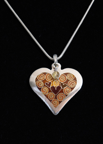 Fine Silver Champlevé and Cloisonné filigree and heart pendant. Complimented by citrine bead dangle and Sterling silver bail. Pendant measures 1 5/8 inches wide by 1 3/4 inches long. Supported on a 16 inch Sterling Silver snake chain. 210.00