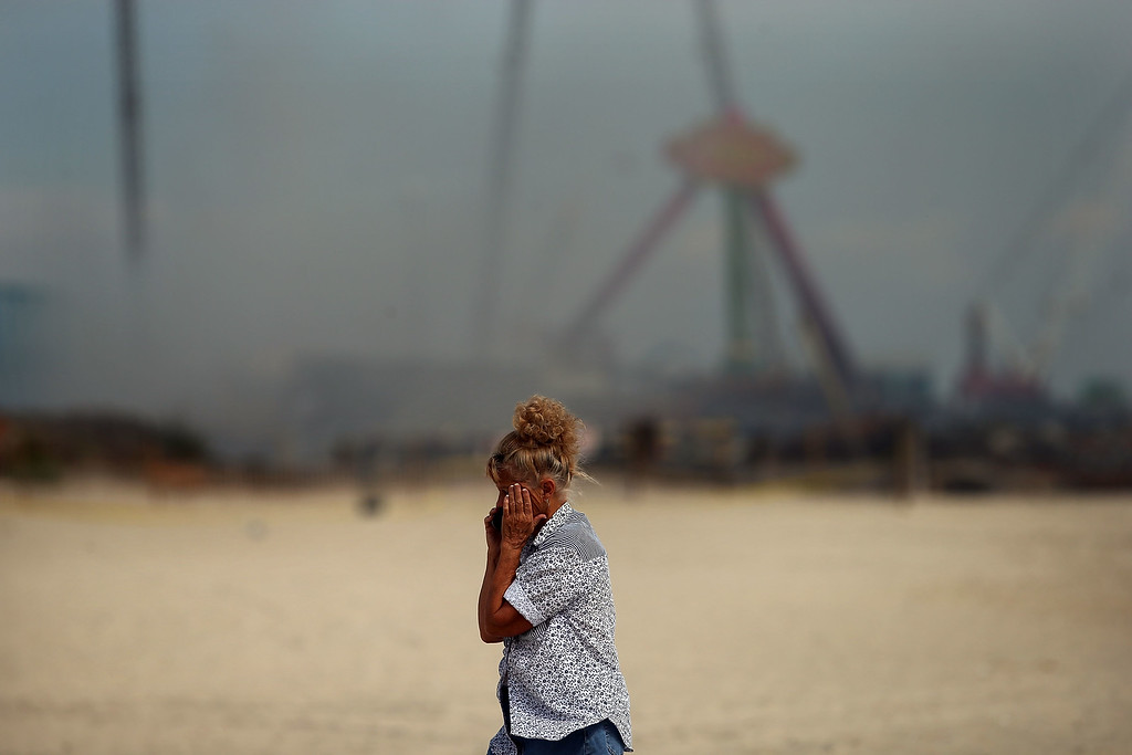 . A woman stands at the scene of a massive fire that destroyed dozens of businesses along an iconic Jersey shore boardwalk on September 13, 2013 in Seaside Heights, New Jersey.   (Photo by Spencer Platt/Getty Images)