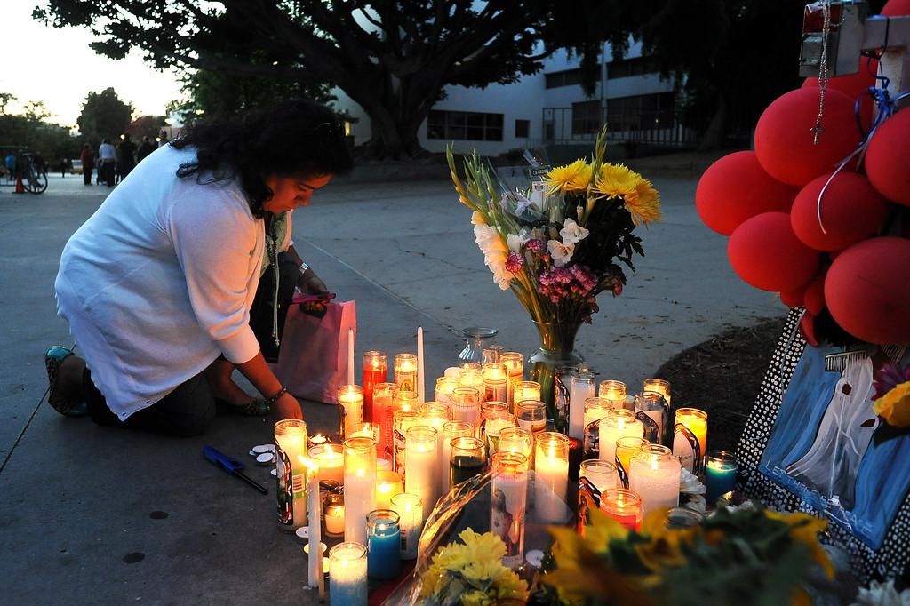 . Sylvia Sanchez lights candles at a memorial at Santa Monica College Monday, June 10, 2013.(Andy Holzman/Los Angeles Daily News)