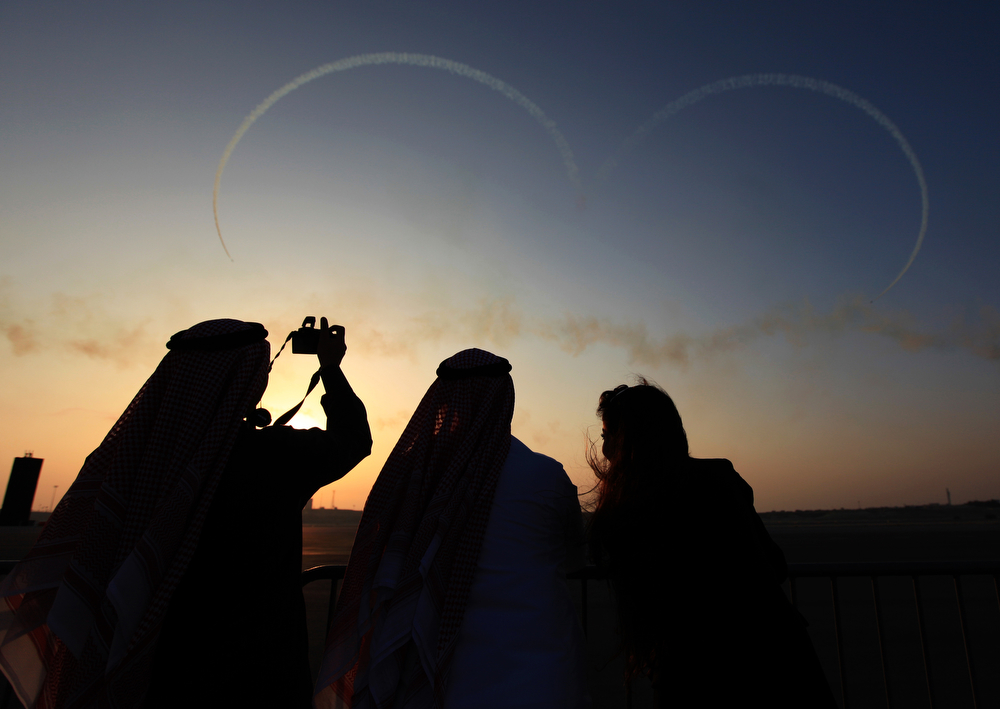 . Visitors watch the Saudi Hawks Display Team draw a heart in the sky Thursday, Jan. 16, 2014, at the Bahrain International Airshow in Sakhir, Bahrain. Bahrain\'s state news agency said the International Airshow opened to announcements of more than $3 billion in agreements. (AP Photo/Hasan Jamali)