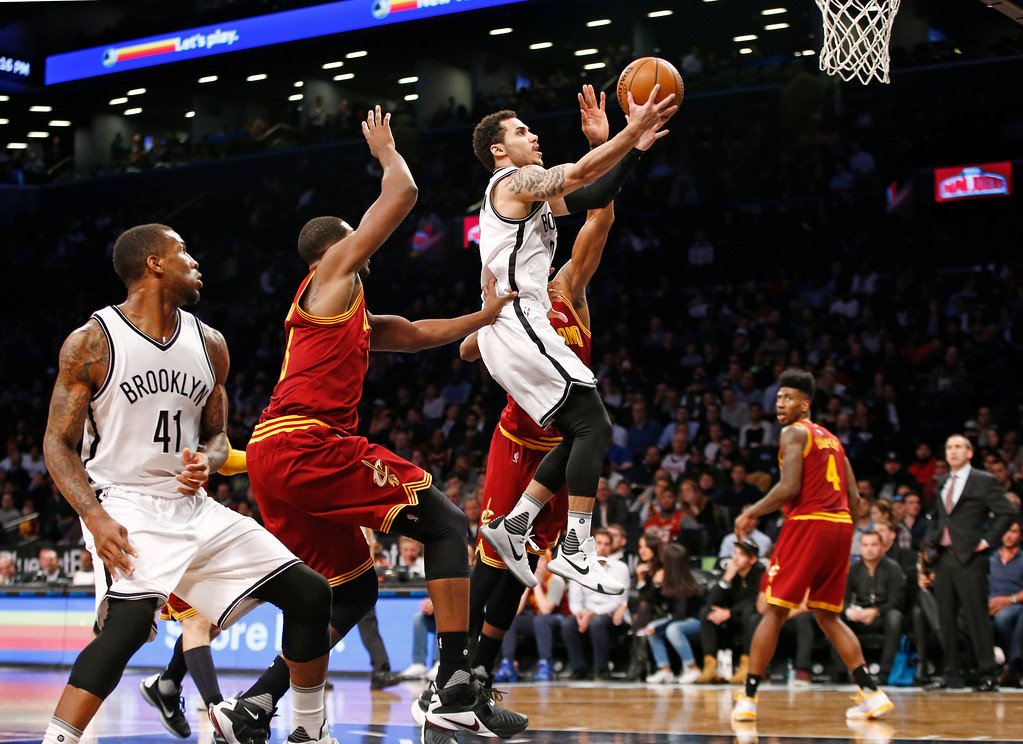 . Brooklyn Nets guard Shane Larkin (0) goes up for a layup with Cleveland Cavaliers center Tristan Thompson (13) and Cavaliers guard James Jones (1) defending in the second half of an NBA basketball game, Wednesday, Jan. 20, 2016, in New York. The Cavaliers defeated the Nets 91-78. Brooklyn Nets forward Thomas Robinson (41) looks on from the floor. (AP Photo/Kathy Willens)