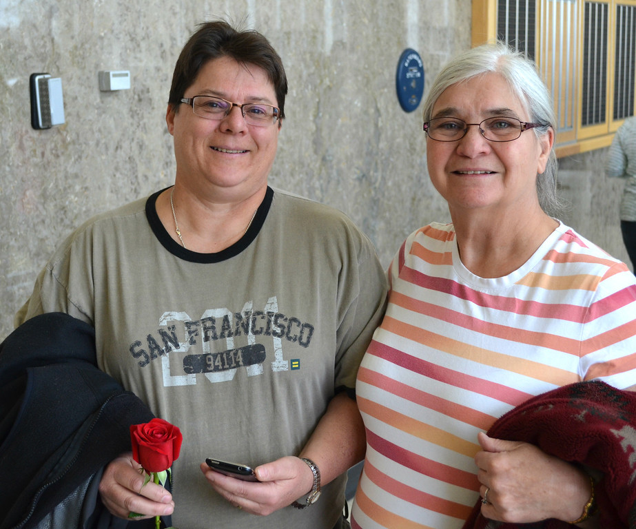 ". Debora Renner, left, holds a rose as she and partner Faith Robinson stand in line for a marriage license at the Oakland County Courthouse on Saturday morning. The two have been together 35 years. ""It\'s wonderful,\"" says Robinson. Dustin Blitchok-The Oakland Press"