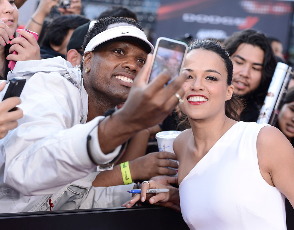 ". Actress Michelle Rodriguez poses for a photo with a fan at the LA Premiere of the ""Fast & Furious 6\"" at the Gibson Amphitheatre on Tuesday, May 21, 2013 in Universal City, Calif. (Photo by Dan Steinberg/Invision/AP)"