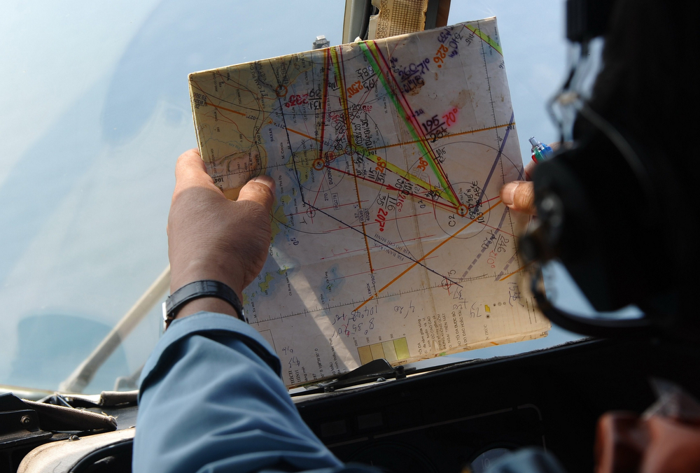 . This picture taken aboard a Vietnamese Air Force Russian-made MI-171 helicopter shows a crew member checking a map during a search flight some 200 km over the southern Vietnamese waters off Vietnam\'s island Phu Quoc on March 11, 2014 as part of continued efforts aimed at finding traces of the missing Malaysia Airlines MH370. Malaysian police said on March 11 one of two suspect passengers who boarded a missing passenger jet was an Iranian illegal immigrant, as relatives of some of the 239 people on board said they were losing hope for a miracle. (HOANG DINH NAM/AFP/Getty Images)