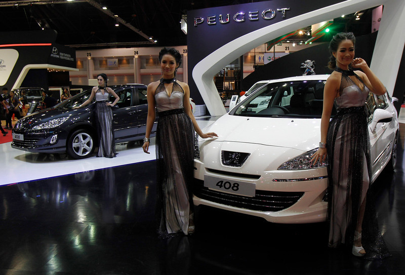 . Models pose beside a Peugeot 408 during a media presentation of the 34th Bangkok International Motor Show in Bangkok March 26, 2013. The Bangkok International Motor Show will be held from March 27 to April 7. REUTERS/Chaiwat Subprasom