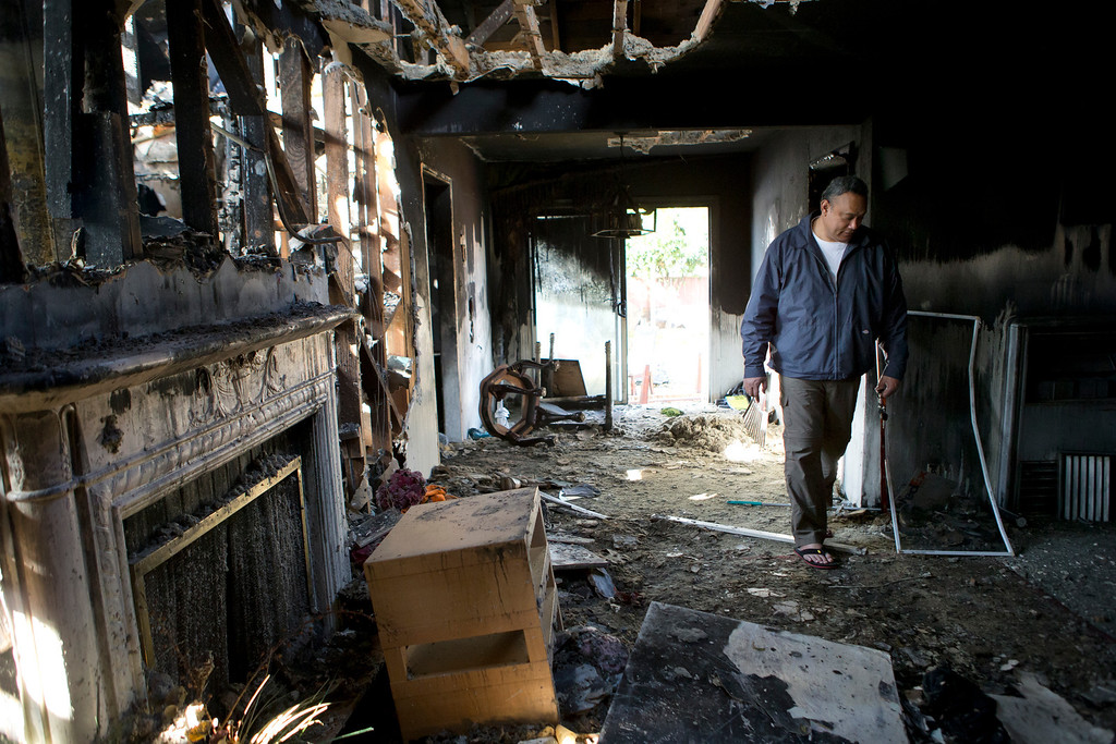 . Uatesoni Paasi walks through his house that was destroyed by a fire in December, in San Mateo, Calif. on Thursday, Jan. 2, 2014.  (LiPo Ching/Bay Area News Group)