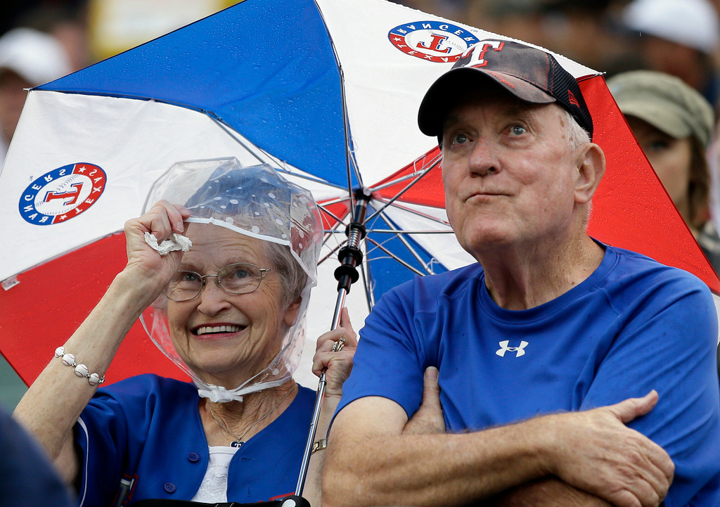 . A pair of Texas Rangers fans shield themselves from a light rain in the first inning of a baseball game against the Detroit Tigers, Tuesday, June 24, 2014, in Arlington, Texas. (AP Photo/Tony Gutierrez)