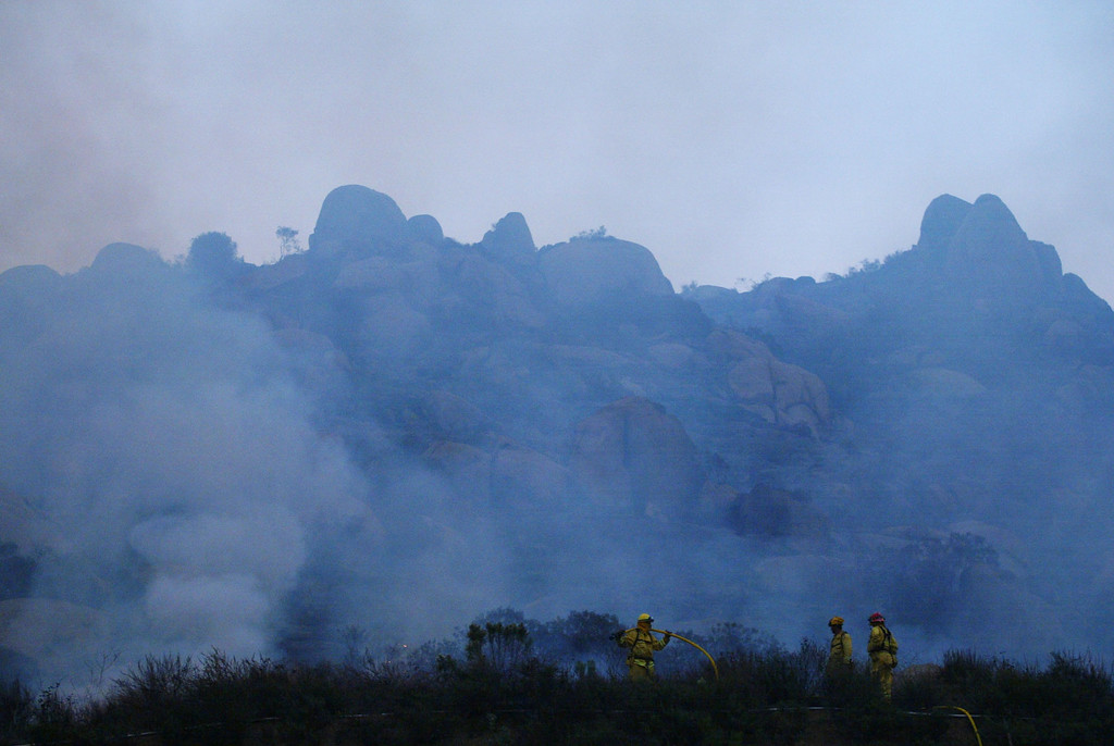 . SAN DIEGO - OCTOBER 27:  Firefighters work to put out the remnants of part of the Cedar Fire in the shadow of charred hills October 27, 2003 near Lakeside in San Diego, California. The death toll stands at 13, with more than 1,000 homes being reduced to ashes as southern California fires continue to burn. Winds have eased a bit, but 30,000 homes remain threatened by the fires, which have charred more than 400,000 acres, according to officials. Davis, who has activated the National Guard, predicted damages will be in the billions of dollars.  (Photo by Donald Miralle/Getty Images)