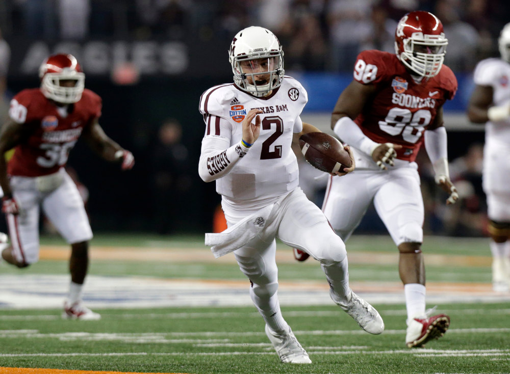 Description of . Texas A&M's Johnny Manziel (2) finds running room as Oklahoma's Javon Harris (30) and Chuka Ndulue (98) give chase in the first half of the Cotton Bowl NCAA college football game Friday, Jan. 4, 2013, in Arlington, Texas. (AP Photo/LM Otero)