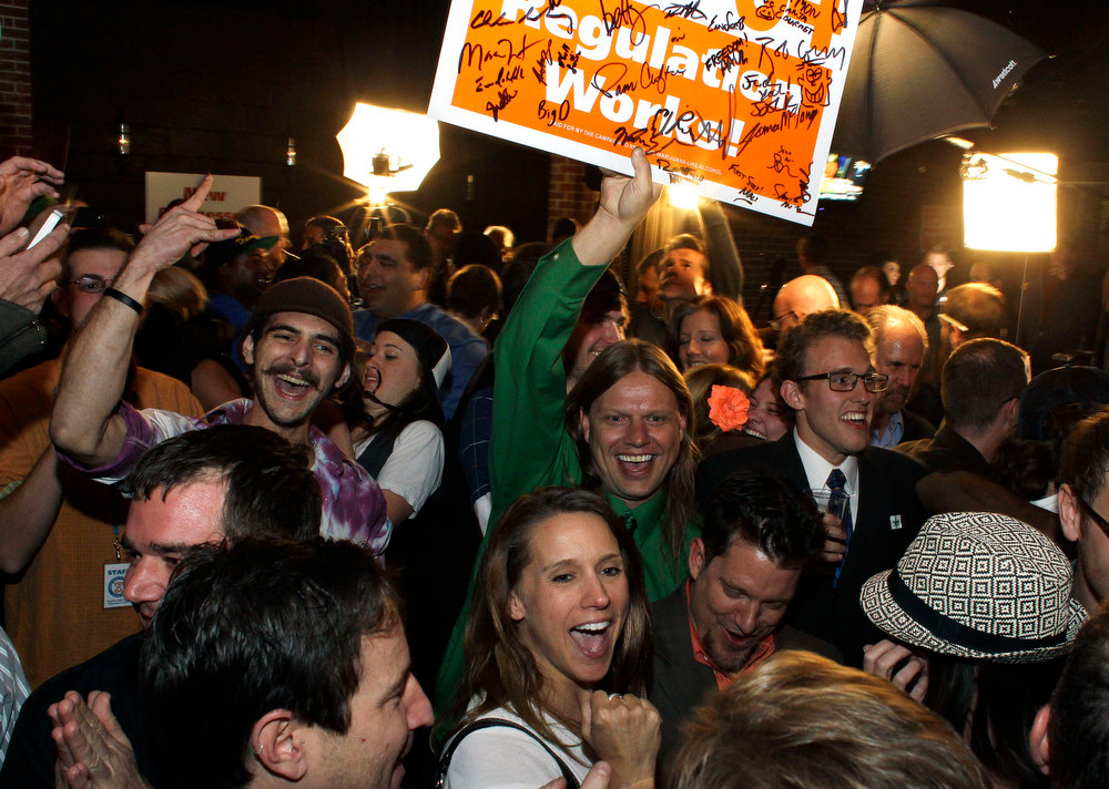 . People attending an Amendment 64 watch party in a bar celebrate after a local television station announced the marijuana amendment\'s passage, in Denver, Colo., Tuesday, Nov. 6, 2012. The amendment would make it legal in Colorado for individuals to possess and for businesses to sell marijuana for recreational use. (AP Photo/Brennan Linsley)