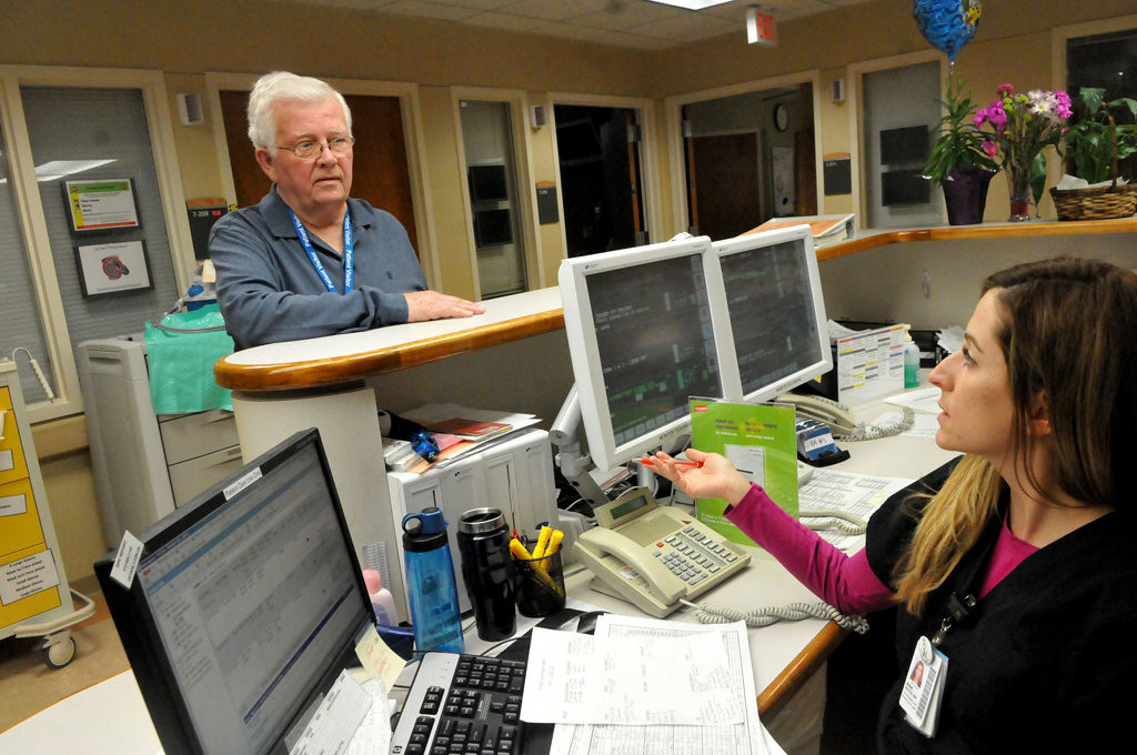 """. Hospital volunteer Jerry Nelson of Shoreview obtains patient names and room numbers from RN Annie Doyle before  visiting  them at the University of Minnesota Medical Center, Fairview. \""""I\'m doing it in her memory and because I understand the real need for it,\"""" Nelson said. (Pioneer Press: John Doman)"""
