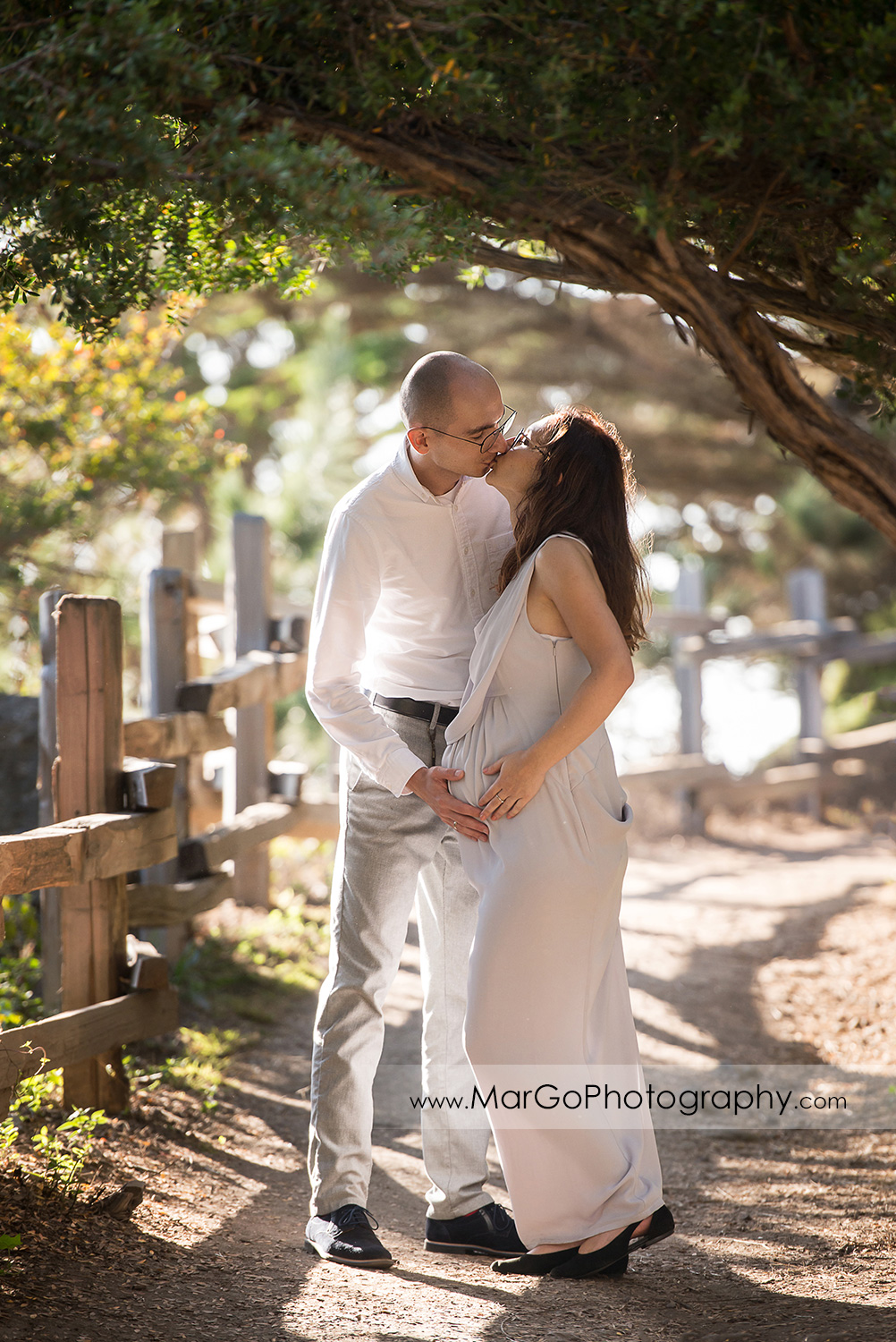 man and pregnant woman in long gray kissing under on the cypress tree