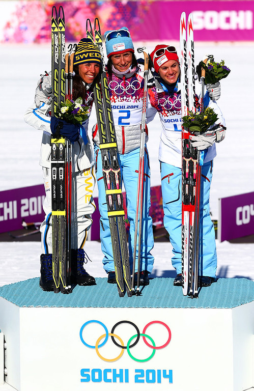 . (L-R) Silver medalist Charlotte Kalla of Sweden, gold medalist Marit Bjoergen of Norway and bronze medalist Heidi Weng of Norway celebrate on the podium during the flower ceremony for the Ladies\' Skiathlon 7.5 km Classic + 7.5 km Free during day one of the Sochi 2014 Winter Olympics at Laura Cross-country Ski & Biathlon Center on February 8, 2014 in Sochi, Russia.  (Photo by Clive Mason/Getty Images)
