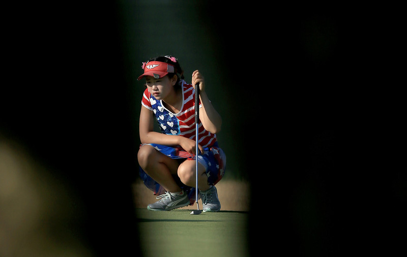 . Lucy Li of the USA who is only 11 years old lines up a putt at the par 4, 14th hole during the first round of the 69th U.S. Women\'s Open at Pinehurst Resort & Country Club, Course No. 2  on June 19, 2014 in Pinehurst, North Carolina.  (Photo by David Cannon/Getty Images)