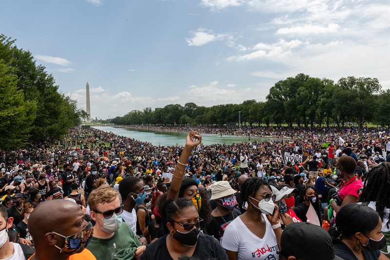 """Demonstrators wearing protective masks march during the """"Get Your Knee Off Our Necks"""" March on Washington in Washington, D.C., U.S., on Friday, Aug. 28, 2020.. The civil rights rally will be headlined by the Reverend Al Sharpton and is expected to bring thousands to the site where Reverend Martin Luther King Jr. delivered his historic """"I Have a Dream"""" speech 57 years ago. Photographer: Eric Lee/Bloomberg"""