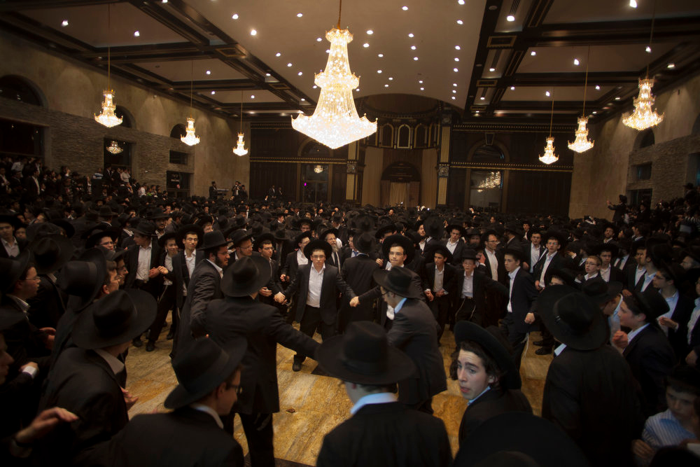 . Ultra Orthodox Jewish men dance in a Synagogue during a celebration in the West Bank Jewish settlement of Modiin Illit, Monday, March 11, 2013. Thousands celebrated the inauguration of a new Torah scroll. (AP Photo/Sebastian Scheiner)