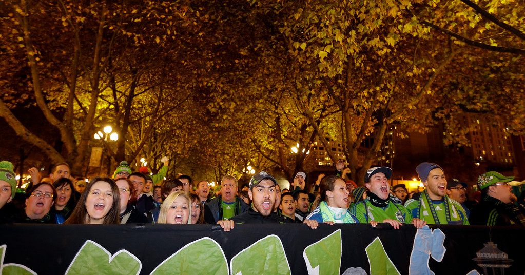 """. Members of the Emerald City Supporters cheer for the Seattle Sounders as they take part in the \""""March to the Match\"""" before a knockout-round match against the Colorado Rapids in the MLS Cup soccer playoffs Wednesday, Oct. 30, 2013, in Seattle. (AP Photo/Ted S. Warren)"""