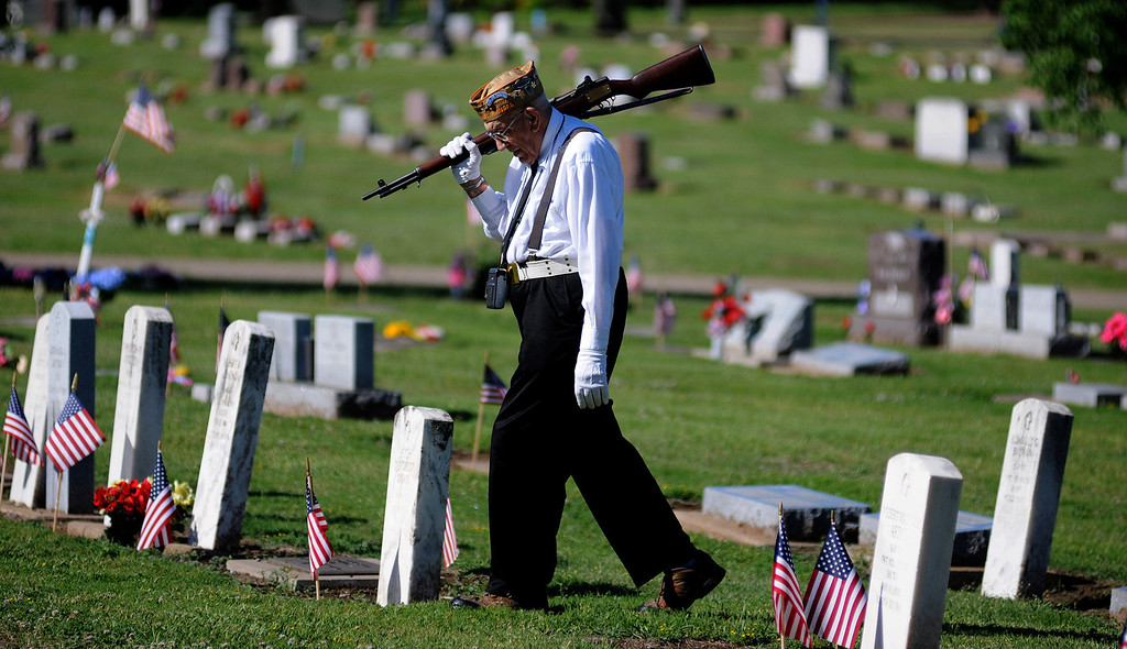 . Bill Siebert, of Salina, a member of the VFW Post 1432 Firing Squad, walks through Gypsum Hill Cemetery to join his squad Monday, May 26, 2014, in Salina, Kan. Siebert served during World War II as a soldier in the 80th Infantry Division in France and Germany.  (AP Photo/Salina Journal, Tom Dorsey)
