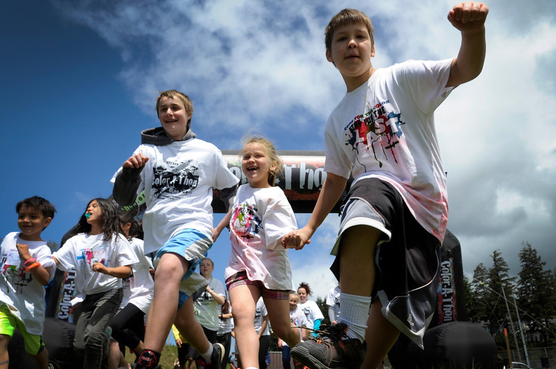 Students run across the starting line for the third annual 3k Open Color Run at North Bend High School in North Bend, Ore. on Saturday, May 6, 2017. The proceeds will go to the upgrade two playgrounds.