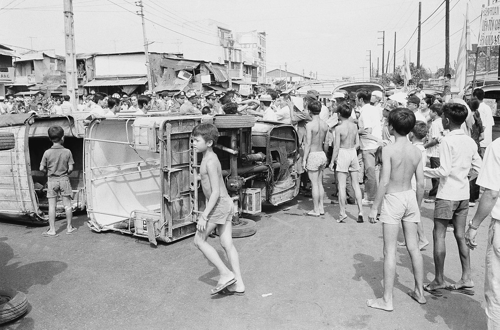 . Saigon youngsters mill around overturned three wheeled minibuses during a demonstration by the vehicles? drivers protesting various economic issues. The protest was one of two which tock place, March 25, 1975 in the South Vietnamese capital Saigon. (AP Photo)