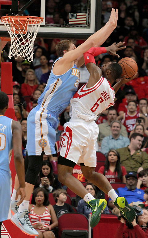 . Denver Nuggets center Timofey Mozgov defends as Houston Rockets forward Terrence Jones goes to the basket during the first half of an NBA basketball game in Houston on Sunday, April 6, 2014. (AP Photo/Richard Carson)