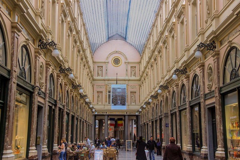 Royal Galleries shopping Mall in Brussels with high end stores. Turn right at the flags and you step onto Rue des Bouchers, a bustling street of wall to wall restaurants with outdoor street side tables.