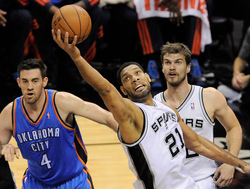 . San Antonio Spurs forward Tim Duncan (21) grabs a rebound as Oklahoma City Thunder forward Nick Collison (4) and Spurs forward Tiago Splitter, of Brazil, watch during the first half of Game 2 of the Western Conference finals NBA basketball playoff series, Wednesday, May 21, 2014, in San Antonio. (AP Photo/Darren Abate)