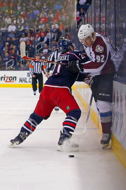 . COLUMBUS, OH - APRIL 1:  James Wisniewski #21 of the Columbus Blue Jackets checks Gabriel Landeskog #92 of the Colorado Avalanche into the boards while battling for control of the puck during the first period on April 1, 2014 at Nationwide Arena in Columbus, Ohio. (Photo by Kirk Irwin/Getty Images)