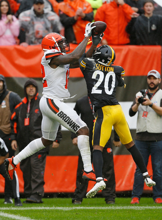 . Cleveland Browns wide receiver Josh Gordon (12) catches a 17-yard touchdown pass under pressure from Pittsburgh Steelers cornerback Cameron Sutton (20) during the second half of an NFL football game, Sunday, Sept. 9, 2018, in Cleveland. (AP Photo/Ron Schwane)