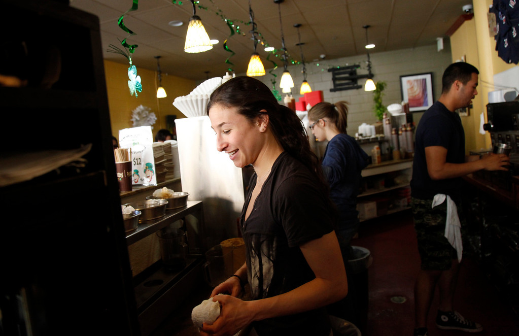 . Hannah Mendelsohn waits on a customer at Philz\' Coffee in San Jose Saturday, March 9, 2013. San Jose�s minimum wage goes into effect Mon. Mar. 11. Businesses who fought the measure are now trying to make lemons out of lemonade by trying to promote San Jose businesses as more ethical and encouraging a buy-local campaign.  (Patrick Tehan/Staff)
