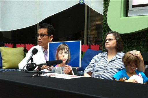 . Dr. Kongkrit Chaiyasate holds up a photo of Charlotte Ponce while talking at a news conference beside Charlotte and her mother, Sharon Ponce, at Beaumont Hospital in Royal Oak, Mich., on Wednesday, Aug. 22, 2012. Charlotte is recovering from the first in a series of reconstructive facial surgeries that the 10-year-old is scheduled to undergo over the next two years. (AP Photo/Mike Householder)