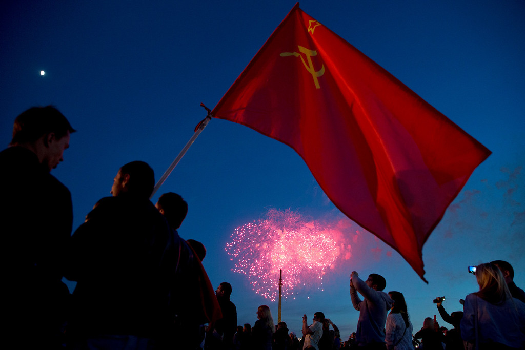 . People hold a Soviet flag and watch  fireworks which mark Victory Day and commemorates the 69th anniversary of the defeat over Nazi Germany,  on Poklonnaya hill in Moscow,  Friday, May 9, 2014.  (AP Photo/Pavel Golovkin)
