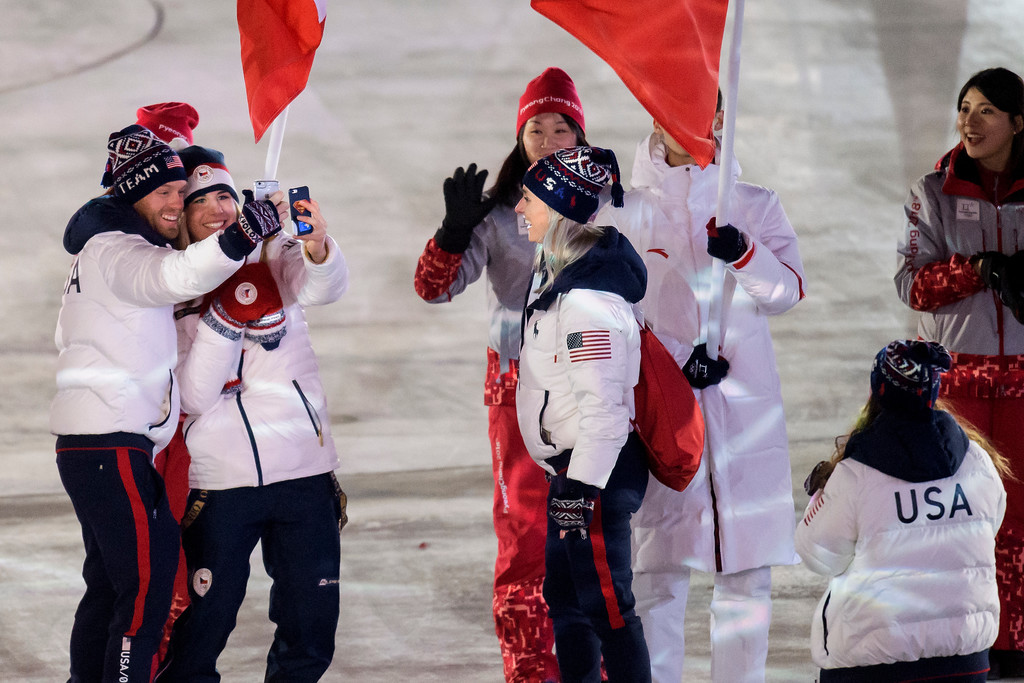 . Ester Ledecka of the Czech Republic, 2nd left, takes photos with U.S. athletes during the closing ceremony of the 2018 Winter Olympics in Pyeongchang, South Korea, Sunday, Feb. 25, 2018. (Jean-Christophe Bott/Keystone via AP)