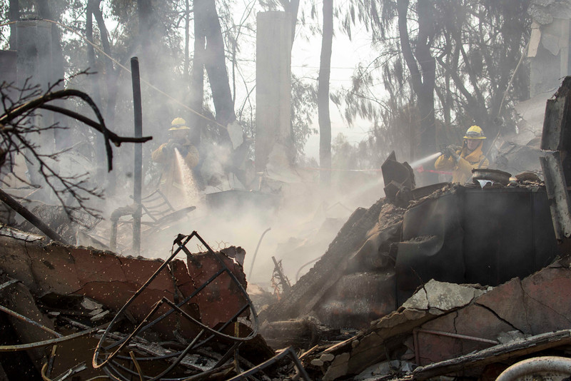 . Firefighters put out hot spots at the Singer Mansion after it burned down during a wildfire burns just north of the San Gabriel Valley community of Glendora, Calif., on Thursday, Jan 16, 2014. Southern California authorities have ordered the evacuation of homes at the edge of a fast-moving wildfire burning in the dangerously dry foothills of the San Gabriel Mountains. (AP Photo/Ringo H.W. Chiu)