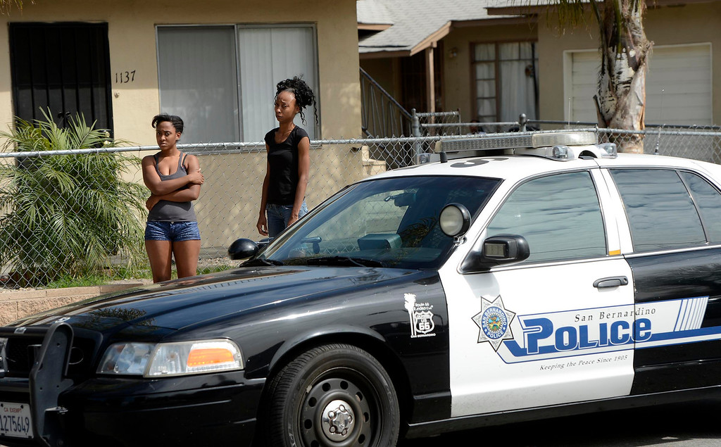 . Two young women watch officers conduct a SMASH sweep along the 1100 block Mayfield Drive in San Bernardino April 4, 2013.  GABRIEL LUIS ACOSTA/STAFF PHOTOGRAPHER.