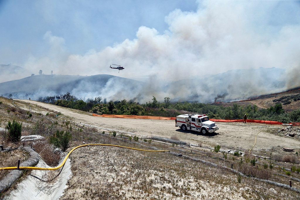 . Firefighters battle a wild fire in the Santa Luz area of San Diego Tuesday, May 13, 2014. Wildfires destroyed a home and forced the evacuation of several others Tuesday in California as a high-pressure system brought unseasonable heat and gusty winds to a parched state that should be in the middle of its rainy season. (AP Photo)