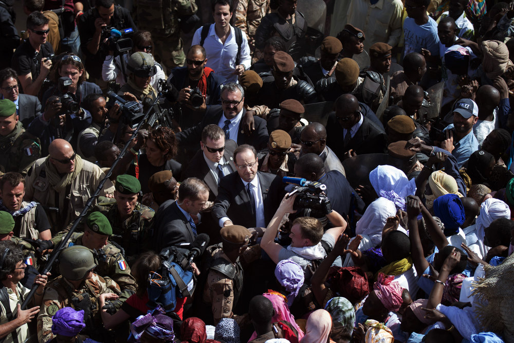 Description of . France\'s President Francois Hollande (C) is welcomed by Malian people as he arrives at Timbuktu, the second step of his one-day visit in Mali, on February 2, 2013. Hollande visits Mali as French-led troops work to secure the last Islamist stronghold in the north after a lightning offensive against the extremists. FRED DUFOUR/AFP/Getty Images