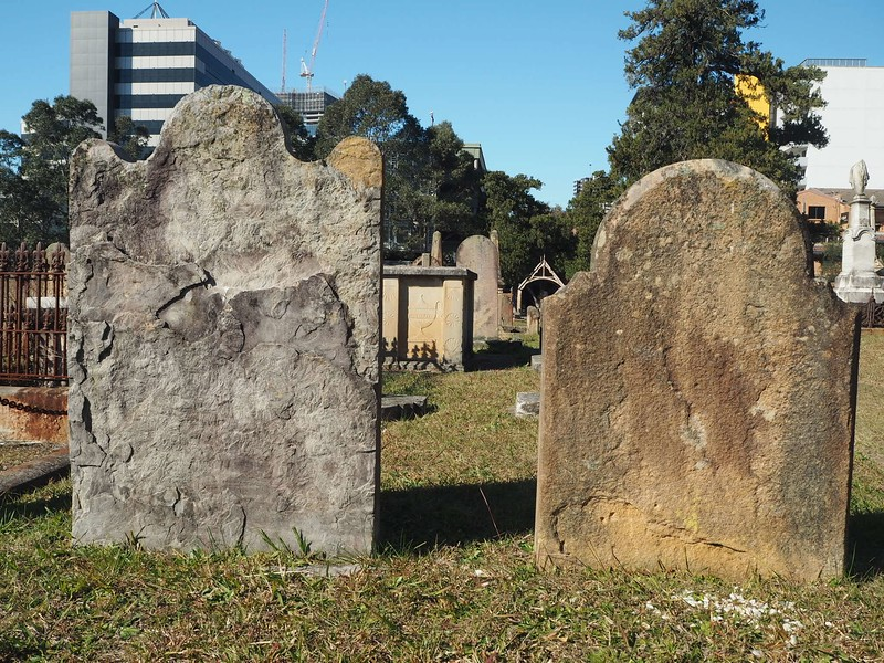 The backs of weather-worn 18th or 19th century grave markers.