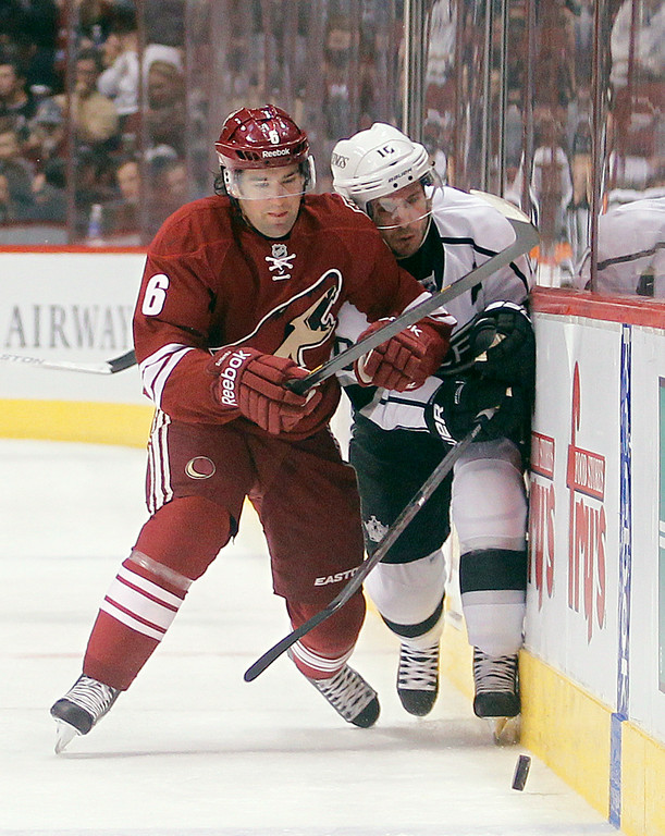 . Phoenix Coyotes defenseman David Schlemko, left, checks Los Angeles Kings center Mike Richards, right, as they chase down a loose puck in the first period of an NHL hockey game Tuesday, April 2, 2013, in Glendale, Ariz. (AP Photo/Paul Connors)