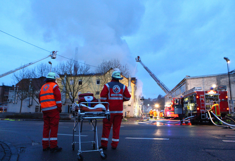 . Rescuers stand near a house in Backnang,  Germany Sunday March 10, 2013.  An early-morning fire on Sunday at the apartment building in southwestern Germany left seven people dead, six of them children, police said.  Authorities were alerted to the blaze in Backnang, a town near Stuttgart, at 4.30 a.m. Police said in a statement that they believe the fire broke out in a second-floor apartment, and said that their investigation is focusing on a heater in the apartment. (AP Photo/dpa, Benjamin Beytekin)