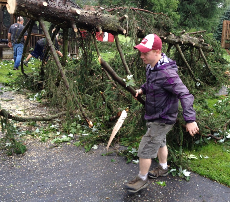 Description of . Josh Herter drags branches as they are cut as he and others clean up at his Grandmothers home on West Main Street and Station Street in Verona following an early morning storm on Wednesday, June 18, 2014. JOHN HAEGER @ONEIDAPHOTO ON TWITTER/ONEIDA DAILY DISPATCH