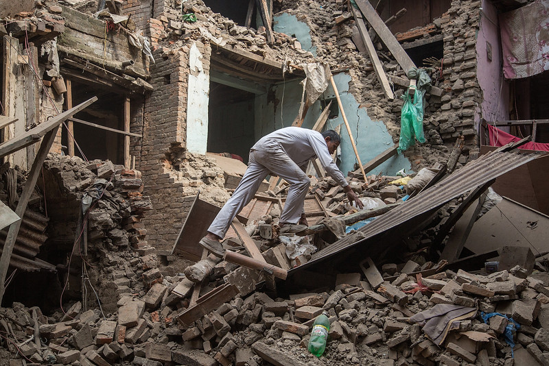 . A man climbs on top of debris after buildings collapsed on April 26, 2015 in Bhaktapur, Nepal. A major 7.8 earthquake hit Kathmandu mid-day on Saturday, and was followed by multiple aftershocks that triggered avalanches on Mt. Everest that buried mountain climbers in their base camps. Many houses, buildings and temples in the capital were destroyed during the earthquake, leaving thousands dead or trapped under the debris as emergency rescue workers attempt to clear debris and find survivors.  (Photo by Omar Havana/Getty Images)