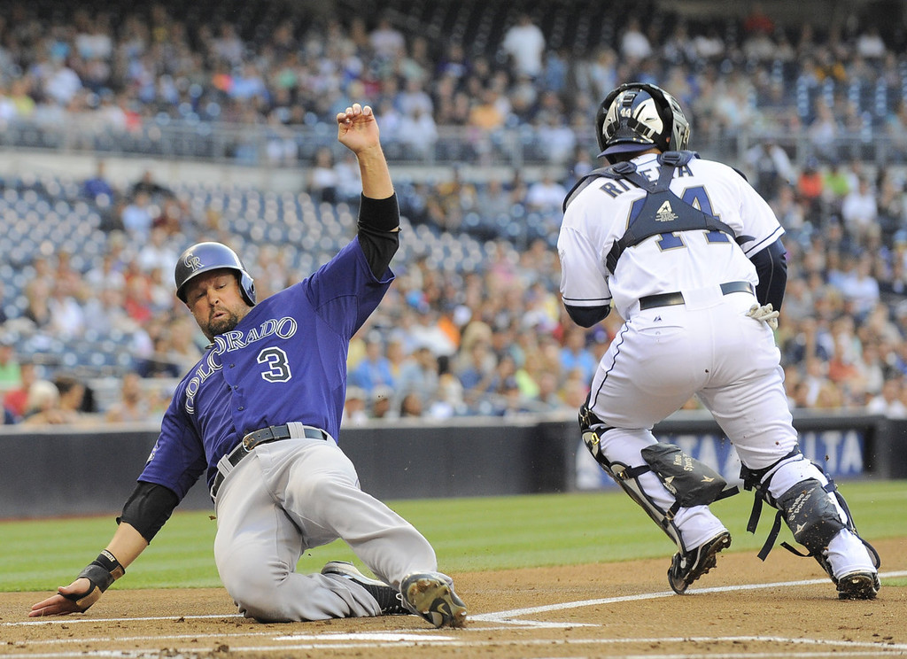 . Michael Cuddyer #3 of the Colorado Rockies scores ahead of the tag of Rene Rivera #44 of the San Diego Padres during the first inning of a baseball game at Petco Park on July 8, 2013 in San Diego, California.  (Photo by Denis Poroy/Getty Images)