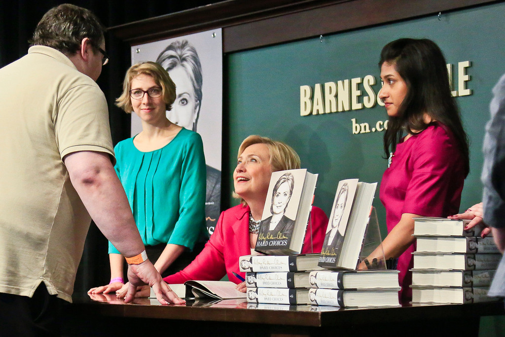 ". Sean Brennan, far left, chats with HiIlary Rodham Clinton, center, before receiving a signed copy of her new book ""Hard Choices,\"" on Tuesday June 10, 2014, at Barnes and Noble bookstore in New York.  Brennan, 41 from Queens, N.Y., was first in line to meet Clinton, spending the night after arriving 2:30 p.m. yesterday.  \""I like Hillary Clinton,\"" said Brennan.  \""There aren\'t many people worth coming out for twenty four hours before hand to see, but she is one of them.\""  (AP Photo/Bebeto Matthews)"